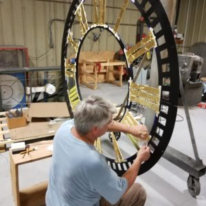 Gold leaf applied on a cast iron tower clock dial in a tower clock manufacturing facility